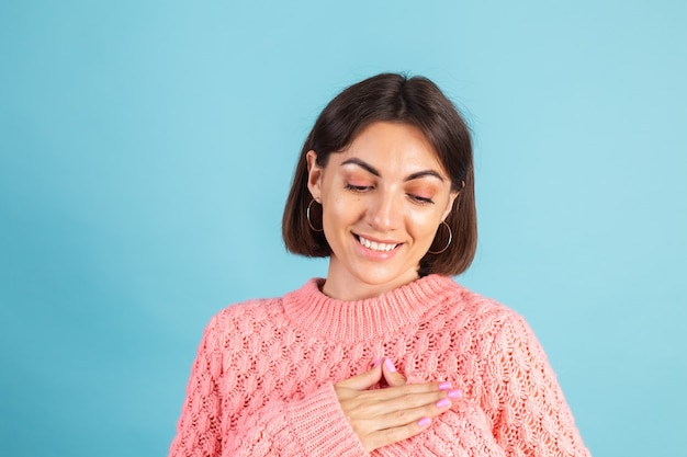 青い壁に分離された暖かいピンクのセーターの若いブルネット