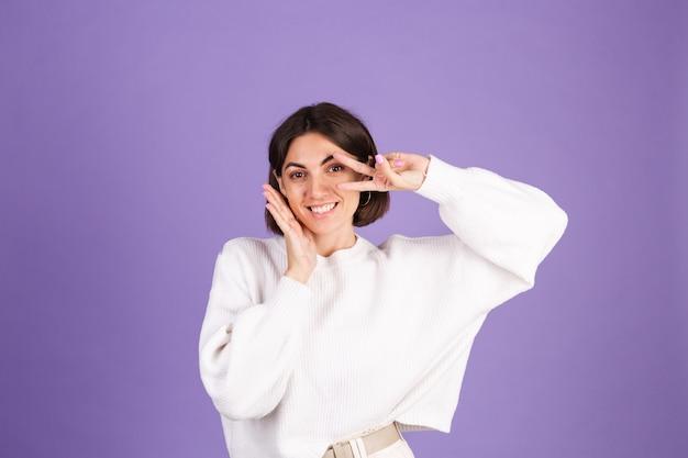 紫色の壁に分離された白いカジュアルセーターの若いブルネット