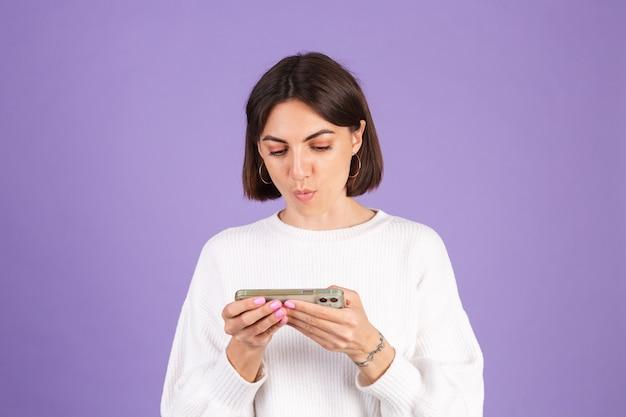 보라색 벽에 고립 된 흰색 캐주얼 스웨터에 젊은 갈색 머리