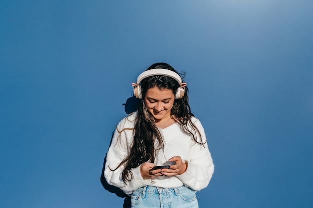 青い背景のヘッドフォンで音楽を聴いている白いセーターの若いブルネット