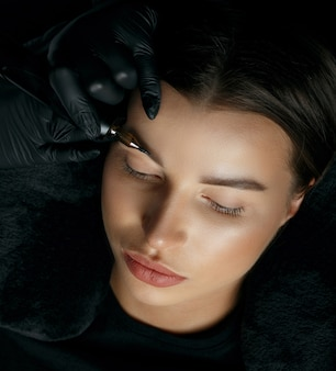 Молодая брюнетка дама, имеющая процедуру перманентного макияжа бровей в студии красоты. вид сверху