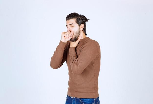 Giovane uomo bruna che tossisce e si tiene la gola.