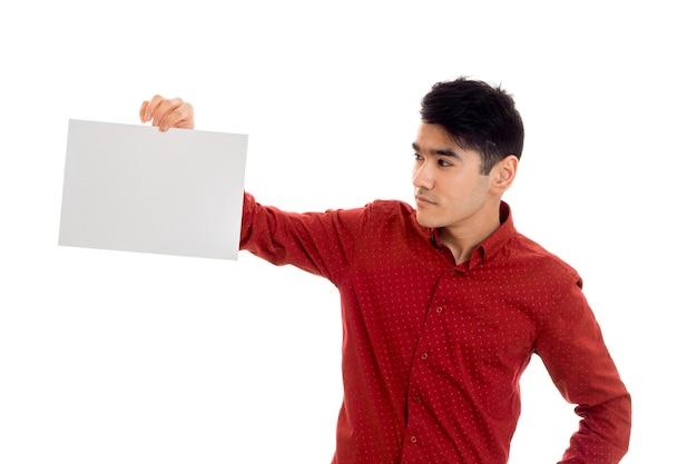 Молодой брюнет в красной футболке позирует с белым плакатом в руке, изолировать на стене