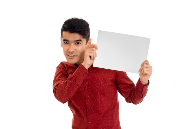 Молодой человек брюнетки в красной футболке позирует с белым плакатом изолировать на белой стене
