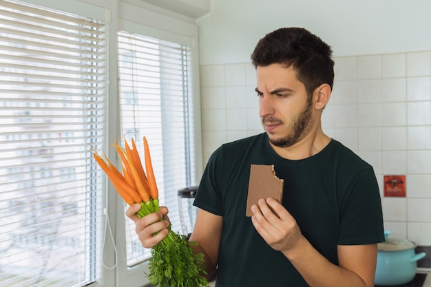 A young brunette man looks at a carrot with disdain and disgust. a person does not lead a healthy lifestyle, he wants to eat sweets and not healthy food.