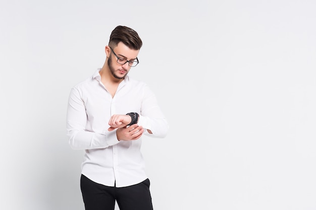 Young brunette man looks at his watch on white wall