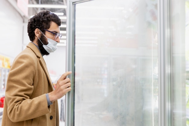 Young brunette man in a medical mask in the supermarket in the department with frozen foods. coronavirus pandemic. space for text.