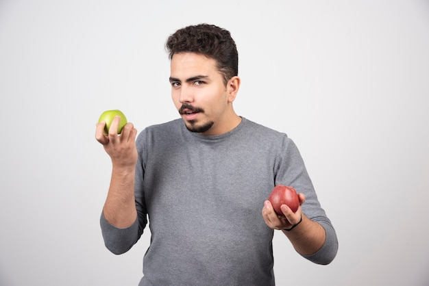 Giovane uomo castana con le mele in posa sul grigio.