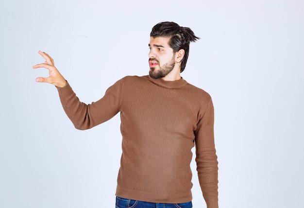 指で小さなサイズのサインをしている手で自信を持って身振りで示すひげを持つ若いブルネットの男。