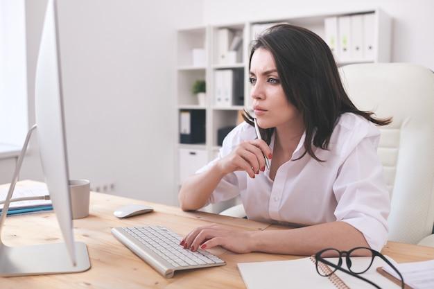 若いブルネットのマネージャーは、机に座ってコンピューターのモニターで情報を読むオンラインプロジェクトに焦点を当てた