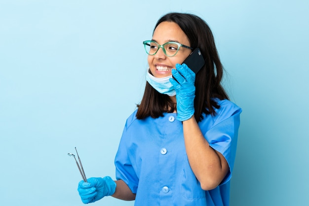 Young brunette mixed race dentist woman holding tools over isolated keeping a conversation with the mobile phone