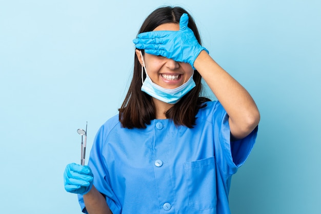 Young brunette mixed race dentist woman holding tools over isolated wall covering eyes by hands and smiling