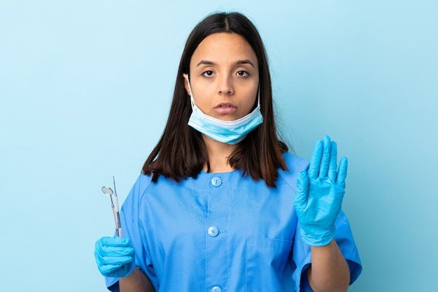 Young brunette mixed race dentist woman holding tools over isolated wall making stop gesture