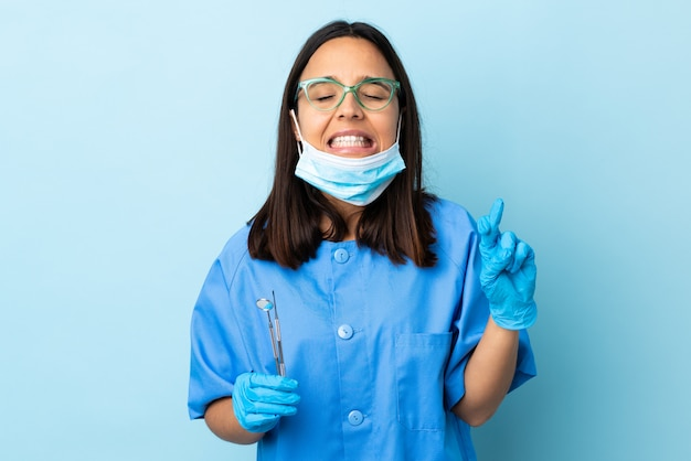 Young brunette mixed race dentist woman holding tools over isolated with fingers crossing and wishing the best