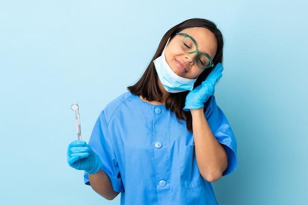 愛らしい表現で睡眠ジェスチャーを作る孤立した壁の上にツールを保持している若いブルネット混血歯科医の女性