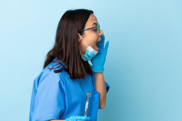 입 벌리고 소리를 통해 도구를 들고 젊은 갈색 머리 혼혈 치과 의사 여자