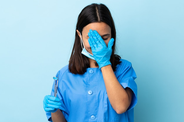 Young brunette mixed race dentist woman holding tools over wall covering eyes by hands