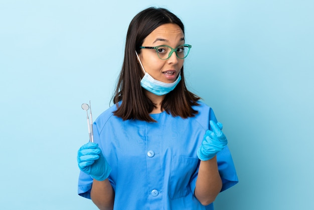 Young brunette mixed race dentist woman holding tools over wall making money gesture