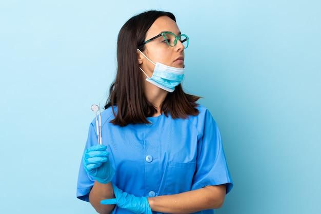 ツールを保持している若いブルネット混血歯科医の女性