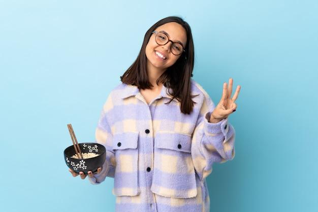 若いブルネットの混血の女性が幸せな青い壁に麺がいっぱい入ったボウルを保持し、指で3つを数える
