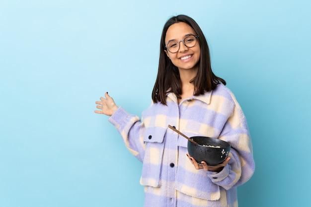 孤立した青い背景の上に麺でいっぱいのボウルを持って来るように誘うために手を横に伸ばしている若いブルネットの混血の女性。