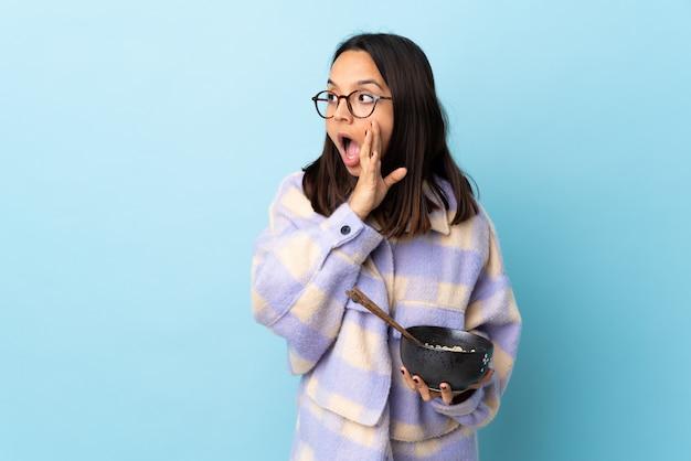 若いブルネットの混血の女性がそばにある驚きのジェスチャーで何かをささやく孤立した青い背景に麺がいっぱい入ったボウルを保持