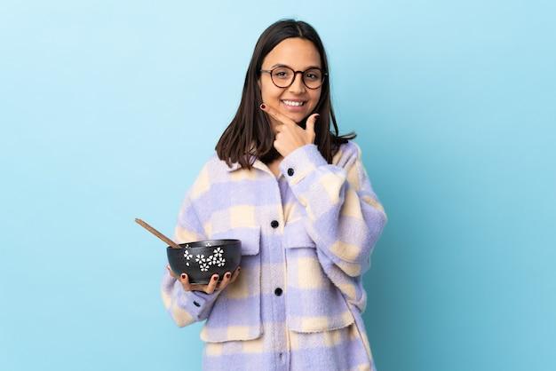 Молодая брюнетка смешанной расы женщина, держащая миску, полную лапши над изолированной синей стеной, счастлива и улыбается.
