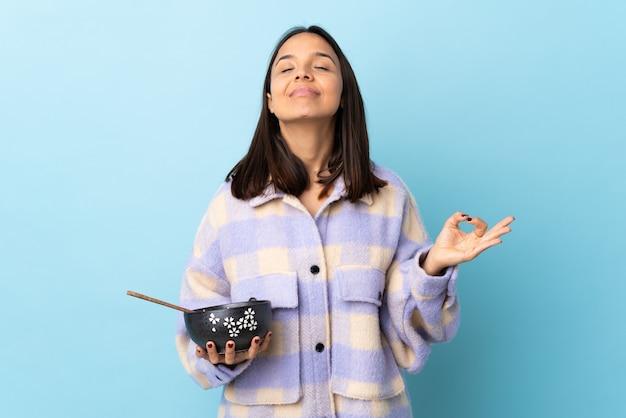 Молодая брюнетка смешанной расы женщина держит миску, полную лапши над изолированной синей стеной в позе дзен.