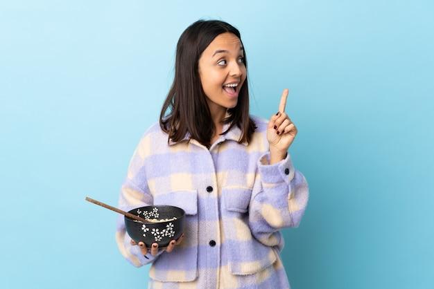 指を持ち上げながら解決策を実現することを意図して孤立した青い壁の上に麺でいっぱいのボウルを保持している若いブルネットの混血の女性。