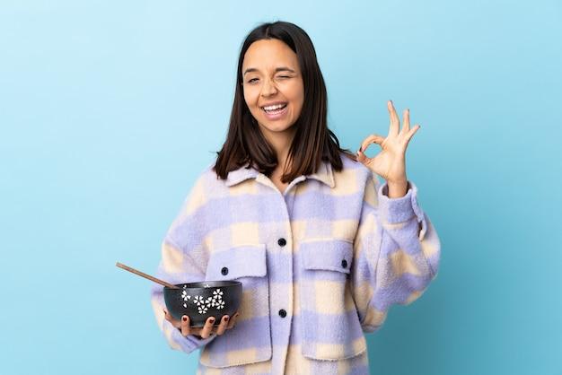 指でokサインを示す孤立した青い壁の上に麺でいっぱいのボウルを保持している若いブルネット混血の女性。