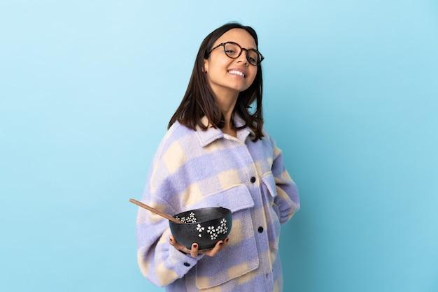 腕を組んで、楽しみにして孤立した青い壁に麺でいっぱいのボウルを保持している若いブルネット混血の女性。