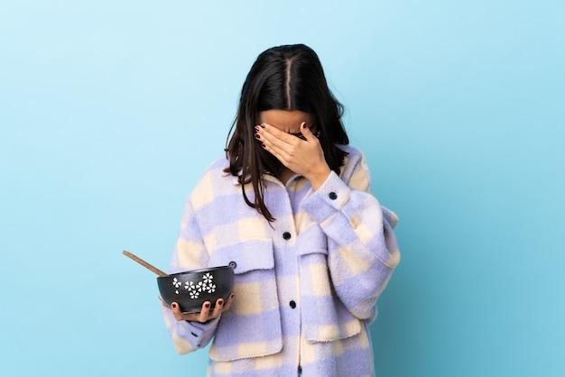 Молодая брюнетка смешанной расы женщина держит миску, полную лапши, над изолированной синей стеной с усталым и больным выражением лица.