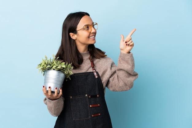 人差し指で素晴らしいアイデアを指している孤立した青い背景の上に植物を保持している若いブルネット混血女性