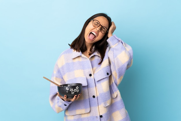 Young brunette mixed race woman holding a bowl full of noodles over blue wall stressed overwhelmed.