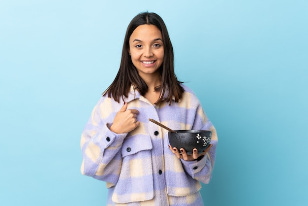 Young brunette mixed race woman holding a bowl full of noodles over blue wall with surprise facial expression