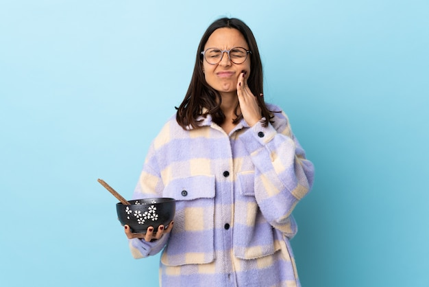 Young brunette mixed race woman holding a bowl full of noodles over blue wall with toothache.