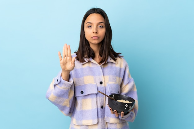 Young brunette mixed race woman holding a bowl full of noodles over isolated blue wall making stop gesture