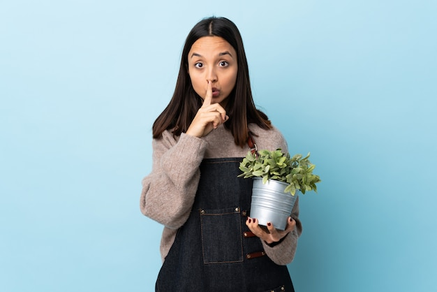 Young brunette mixed race woman holding a plant over isolated blue wall showing a sign of silence gesture putting finger in mouth