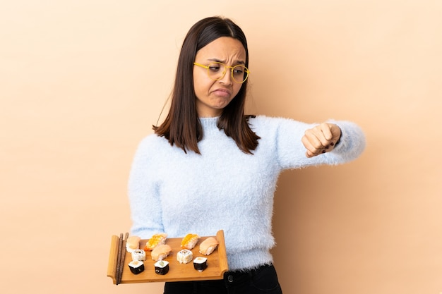 Young brunette mixed race woman holding sushi over isolated background making the gesture of being late