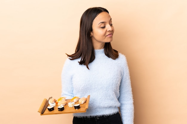 Young brunette mixed race woman holding sushi over isolated wall having doubts while looking side