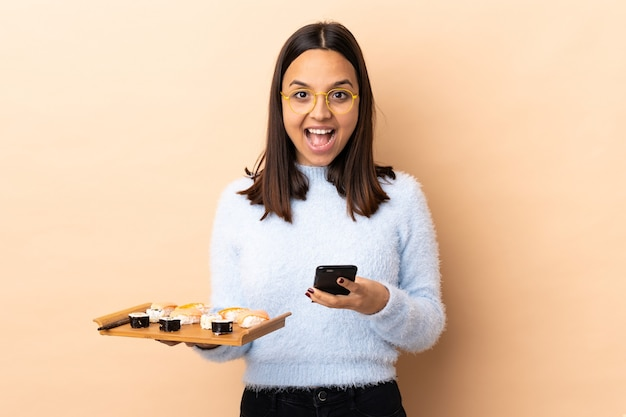 Young brunette mixed race woman holding sushi over isolated wall surprised and sending a message