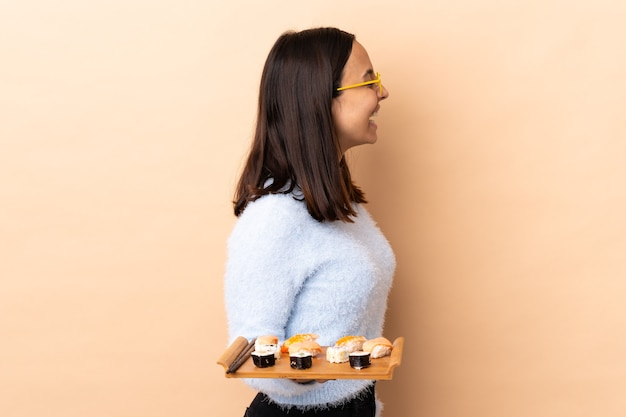 Young brunette mixed race woman holding sushi isolated