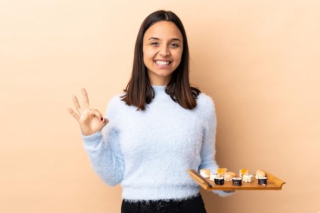 두 손으로 확인 표시를 보여주는 격리 된 배경 위에 초밥을 들고 젊은 갈색 머리 혼혈 여자