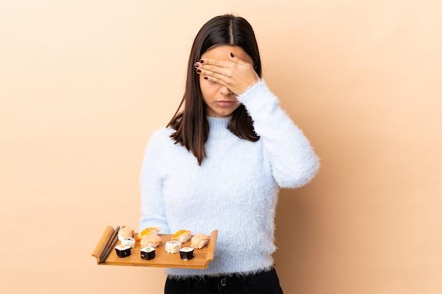 젊은 갈색 머리 혼합 된 인종 여자 손으로 고립 된 덮고 눈 위에 초밥을 들고. 무언가를보고 싶지 않다