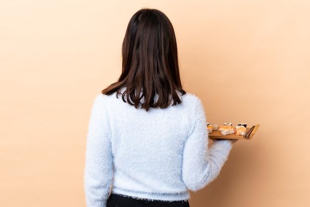 後ろの位置で孤立した壁に寿司を保持している若いブルネット混血の女性