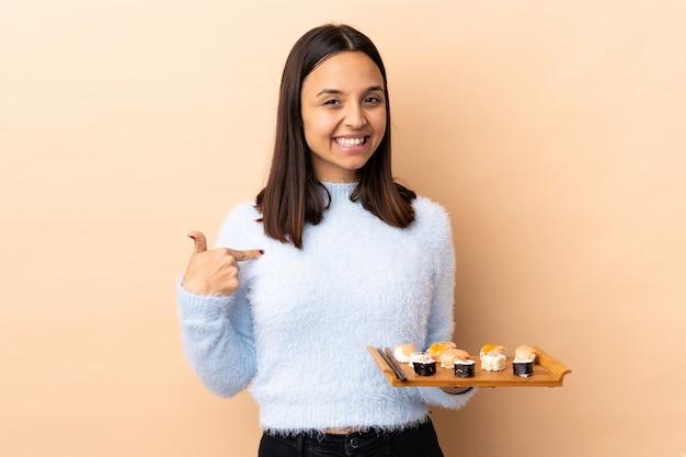Молодая брюнетка смешанной расы женщина держит суши над изолированной стеной гордый и самодовольный