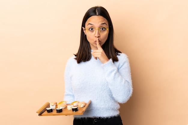 孤立した壁に寿司を持っている若いブルネットの混血の女性は、口に指を入れて沈黙のジェスチャーの兆候を示しています