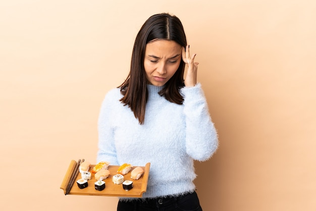 頭痛のある孤立した壁に寿司を保持している若いブルネット混血の女性