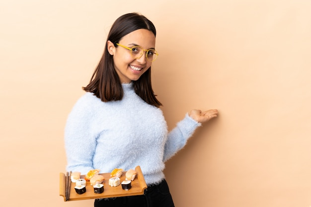 来て招待するために側に手を伸ばす壁を越えて寿司を保持している若いブルネットの混血女性