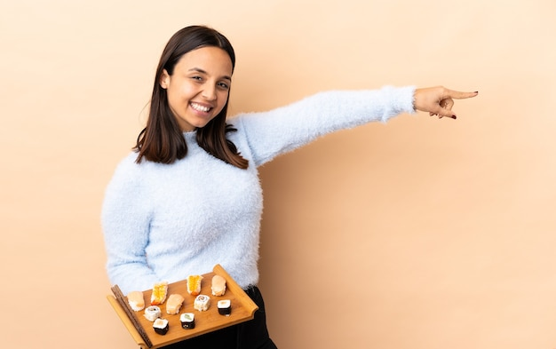 Young brunette mixed race woman holding sushi pointing finger to the side and presenting a product